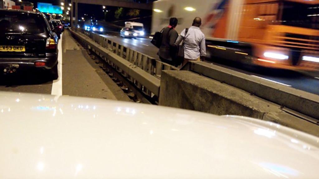 Couple run across six-lane motorway to escape traffic jam