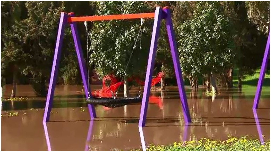 A swing set sits deep in floodwaters. (9NEWS)