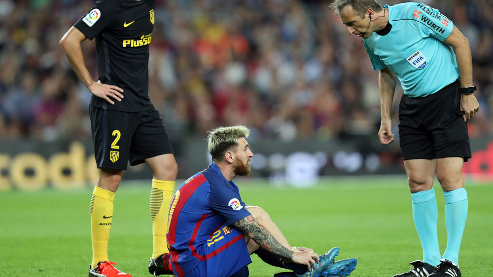 Lionel Messi suffers an injury against Atletico Madrid.(AFP)
