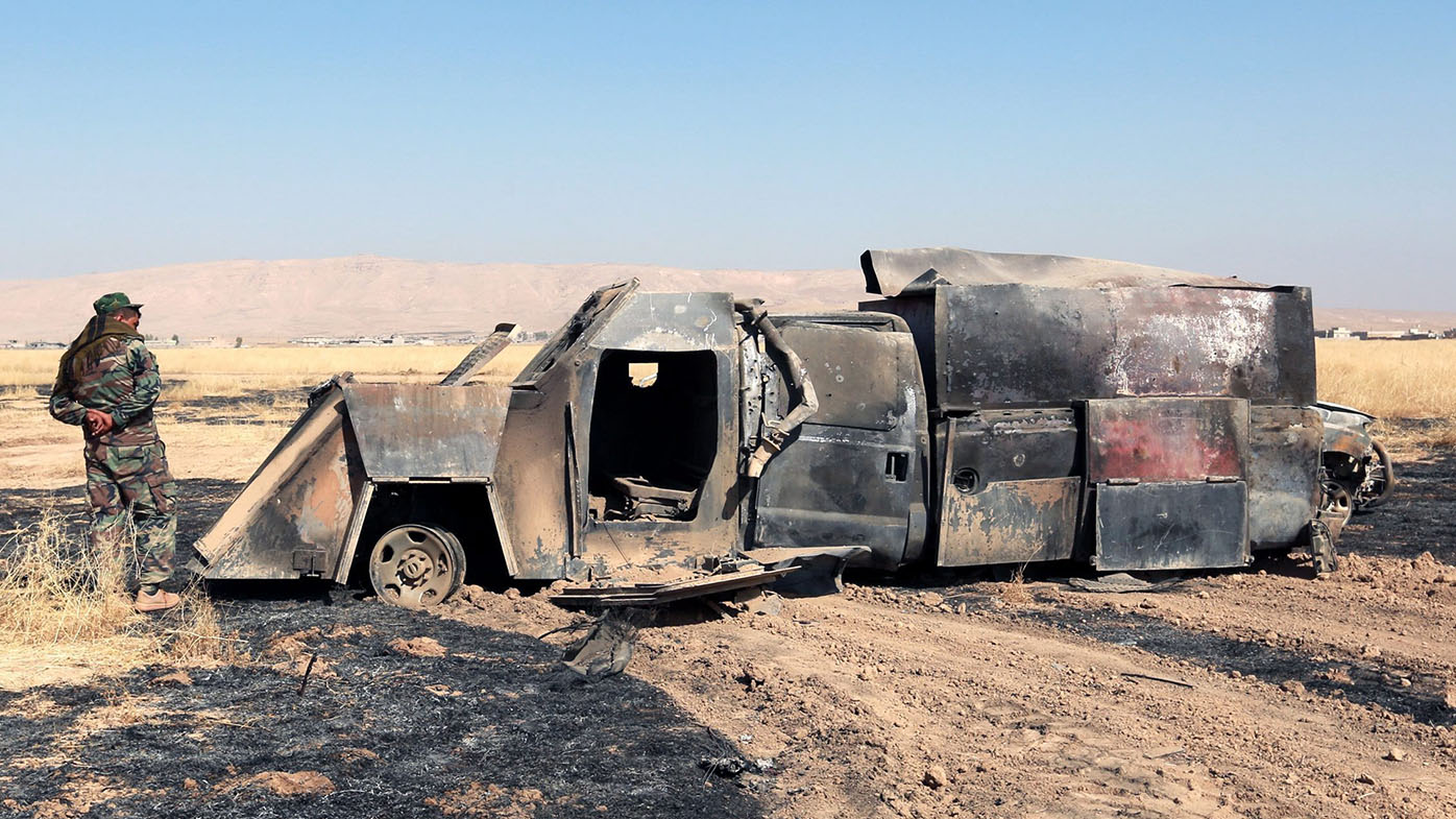 A Peshmerga soldier inspects burnt truck which was used by Islamic State militants after a heavy clashes with Iraqi forces. (AAP)