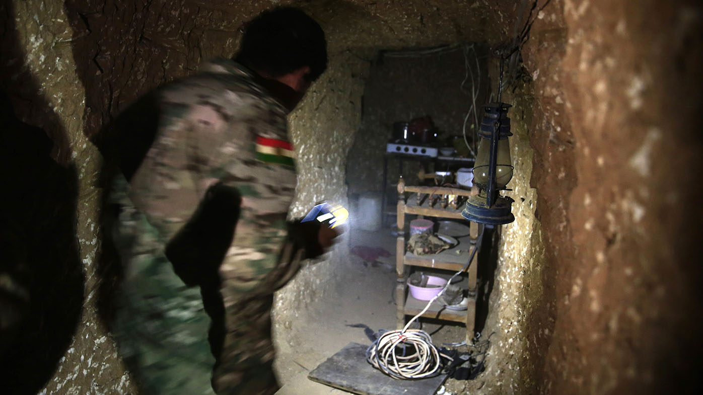 A peshmerga fighter walks through the kitchen of an underground tunnel made by ISIL fighters. (AAP)