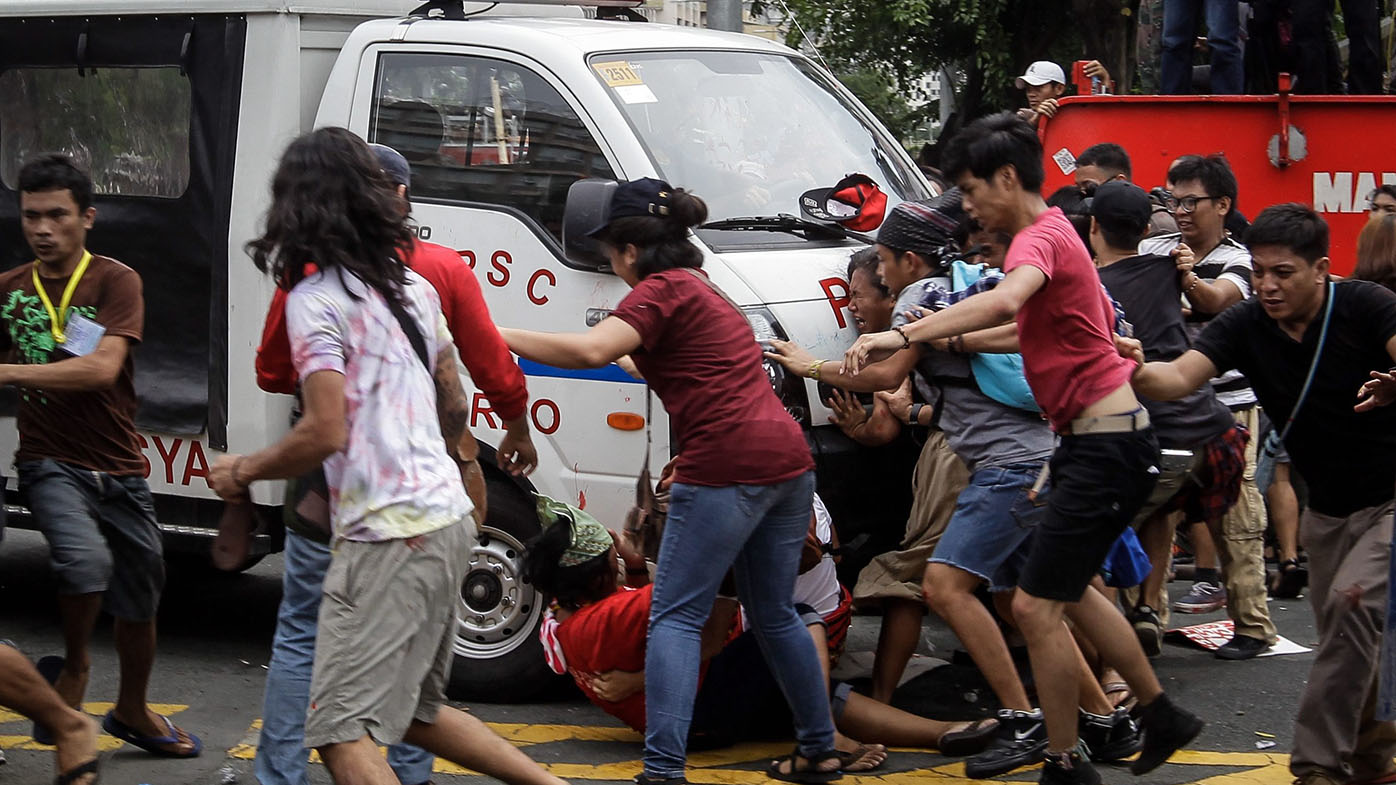 A police mobile runs over protesters during a protest in front of the US Embassy in Manila. (AAP)