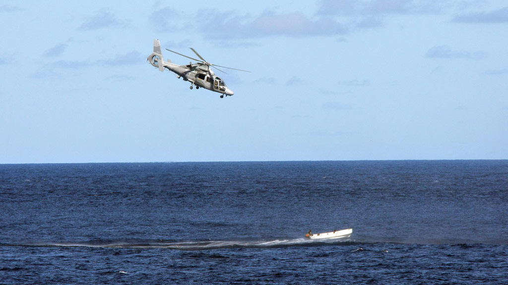 "A French Navy ""Panther"" helicopter chases a boat carrying suspected Somali pirates on May 3, 2009. (AFP)"