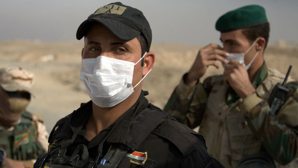Iraqi troops wear masks as they guard a checkpoint near the village of Awsaja, Iraq