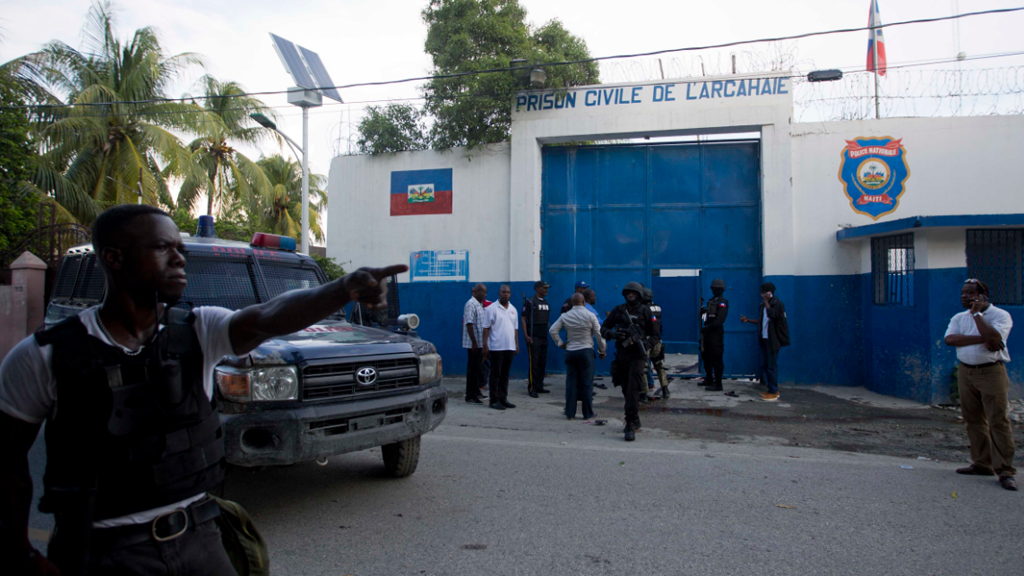 Police gather at the Civil Prison after some inmates escaped in the coastal town of Arcahaiea, Haiti. (AAP)