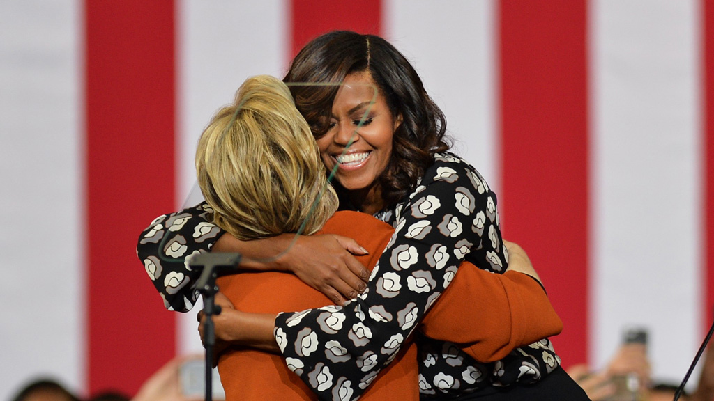 Democratic presidential candidate Hillary Clinton (L) and US First Lady Michelle Obama (R) hug during a presidential campaign event on October 27, 2016. (AFP)