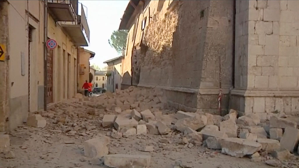 In this image made from video, bricks fallen from a damaged building block a street in Norcia, Italy. (AAP)