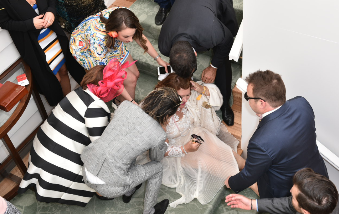 Staff rush to the aid of billionaire Gina Rinehart after she falls down stairs in a Melbourne Cup marquee. (AAP)