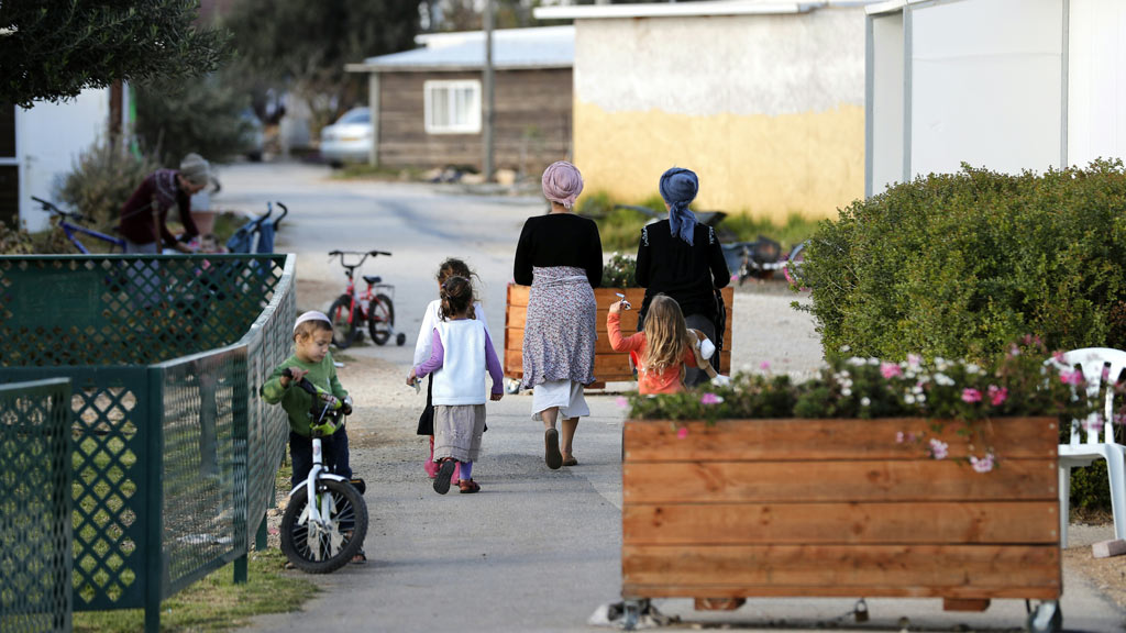 A picture taken on November 17, 2016 shows families in a street of the settlement outpost of Amona, which was established in 1997, in the Israeli-occupied West Bank. (AFP)