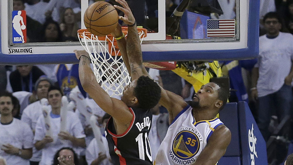 Kevin Durant blocks a dunk attempt from DeMar DeRozan. (AAP)