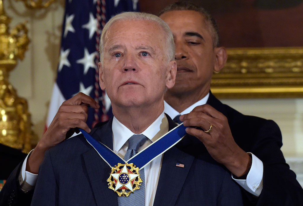 President Barack Obama presents Vice President Joe Biden with the Presidential Medal of Freedom during a ceremony in the State Dining Room of the White House in Washington. (AAP)