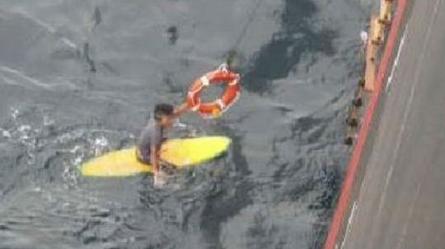 Stranded surfer survives night at sea clinging to board