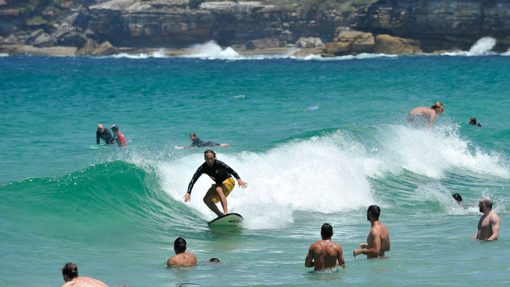 Many sought respite from yesterday's blistering heat by hitting the beach. (AAP)