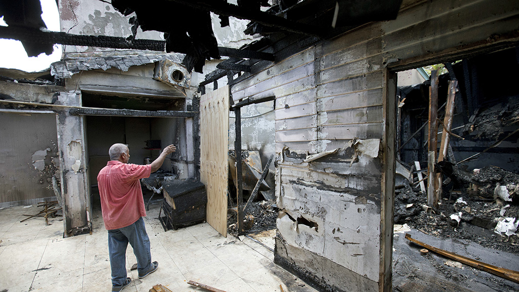 Farhad Khan, who has attended the Islamic Center of Fort Pierce for more than seven years, shows its charred remains. (AAP)
