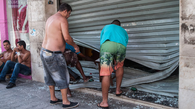 A shopkeeper finds a security door damage in looting after Vitoria police went on strike. (Photo: AFP)