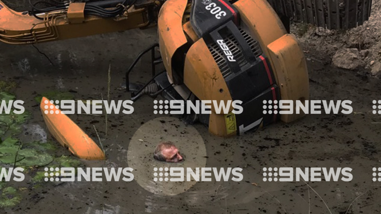 Mr Miller was trapped under his excavator with just his face above the water. (9NEWS)