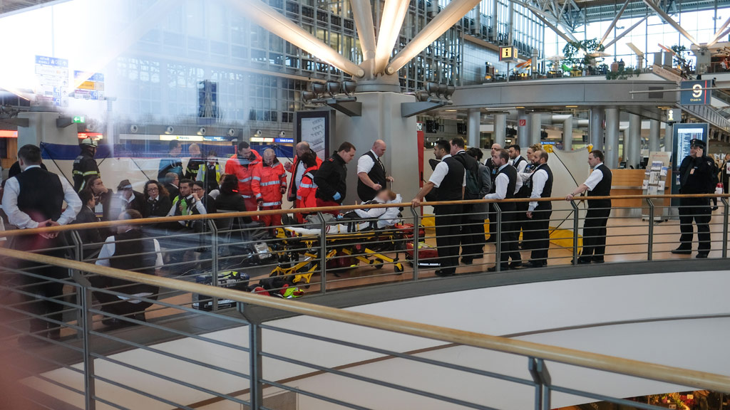 Paramedics look after a person who fell ill after a small permeated Hamburg airport. (AFP)