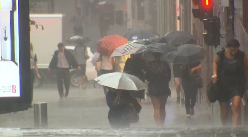 Pedestrians are lashed with rain in the CBD. (9NEWS)