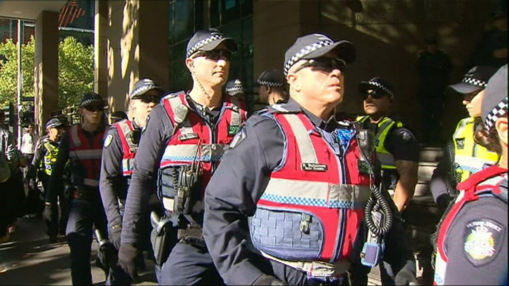 Scores of police lined the street. (9NEWS)