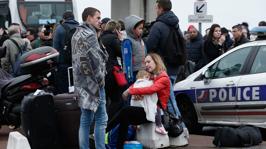 Evacuated travelers wait outside the Orly airport. (AAP)