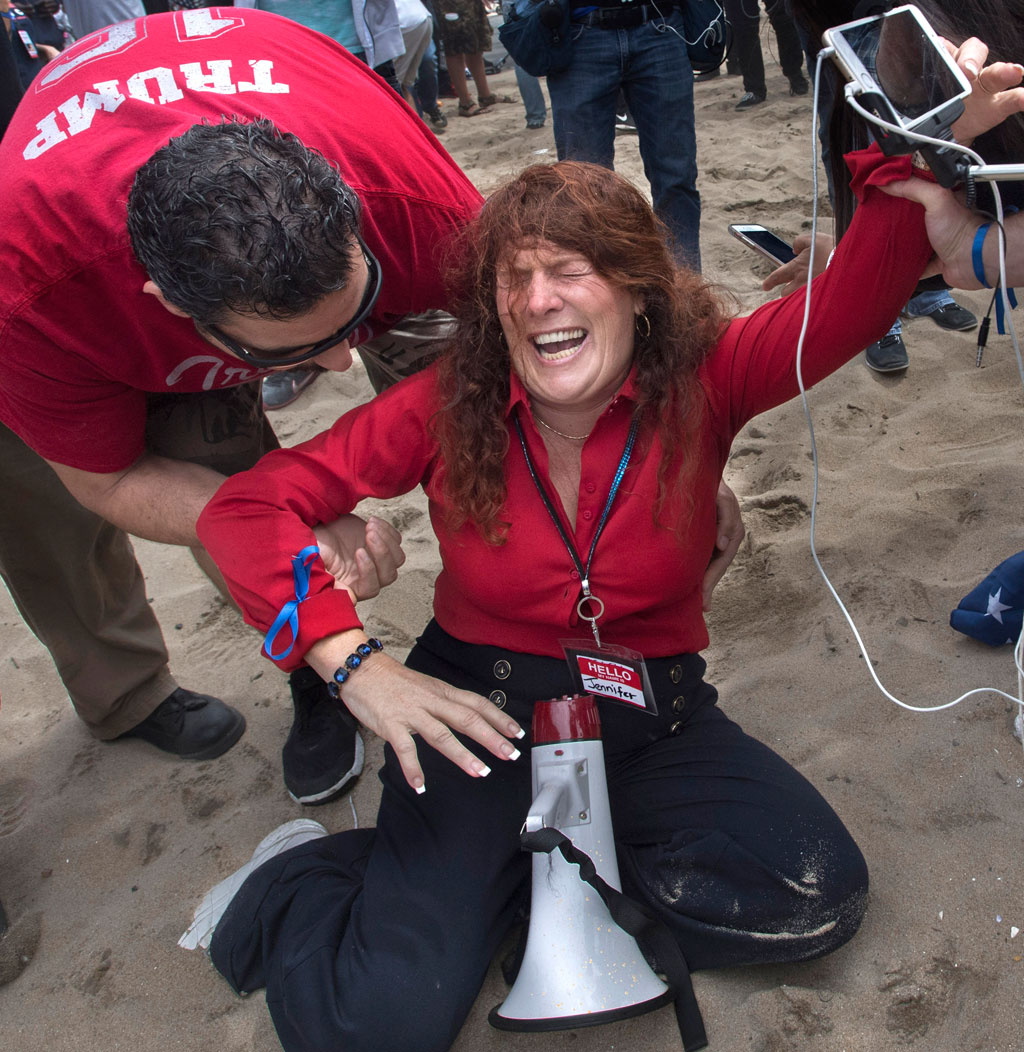 Jennifer Sterling, one of the organizers of the pro-Donald Trump rally reacts after getting hit with pepper spray. (AAP)