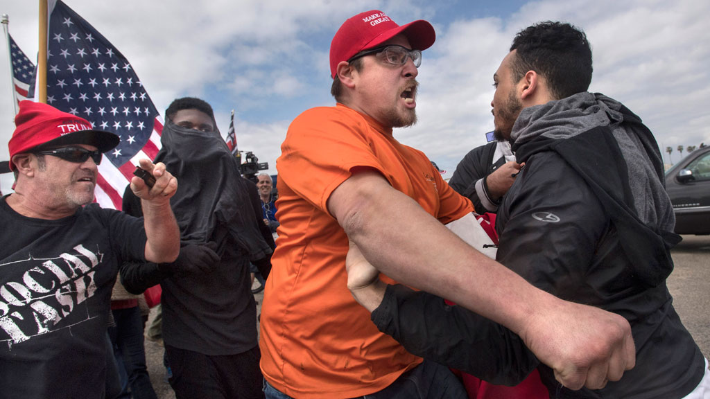 A supporter of President Donald Trump, center, clashes with an anti-Trump protester. (AAP)