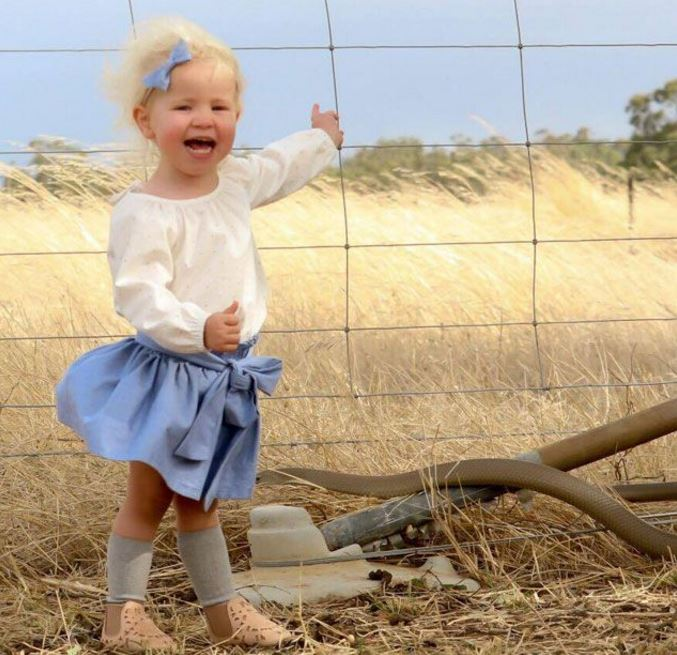Little girl photobombed by huge venomous snake