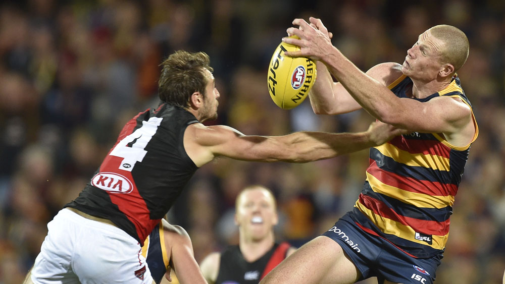 Essendon's Jobe Watson tries to spoil a Sam Jacobs marking attempt. (AAP)