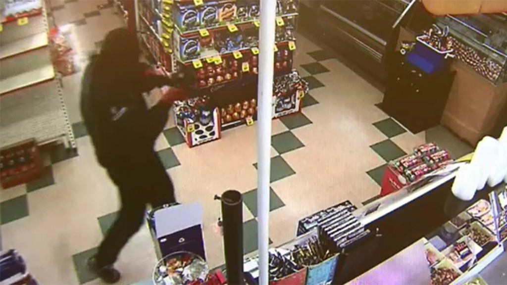 The masked offender was shown pointing a rifle at the teen girl. (9NEWS)