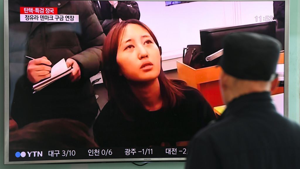 """People watch a screen showing a news report on the arrest of Chung Yoo-Ra, the 20-year-old daughter of the woman dubbed South Korea's """"Rasputin"""" on January 3, 2017. (AFP)"""