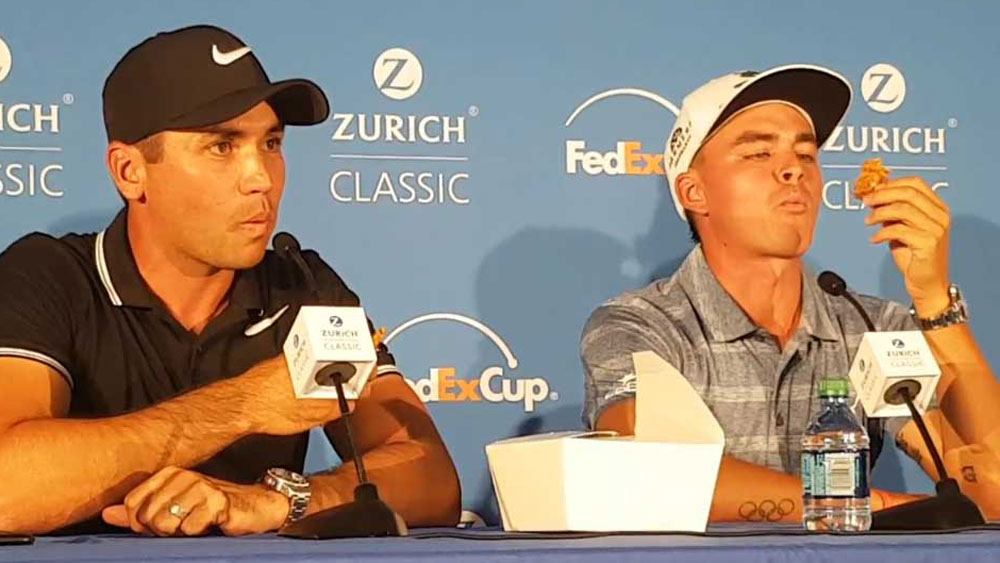Jason Day and Rickie Fowler share an Anzac biscuit in New Orleans.