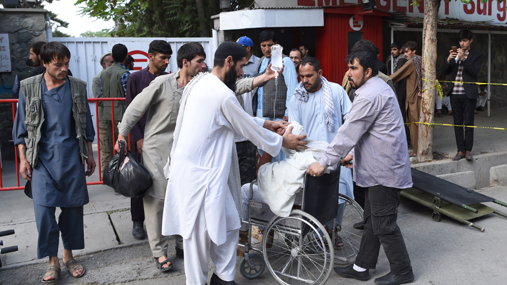 Afghan relatives push the wheelchair of a wounded man following a series of explosions that targeted the funeral of a politician's son who was killed during an anti-government, in Kabul. (AFP)