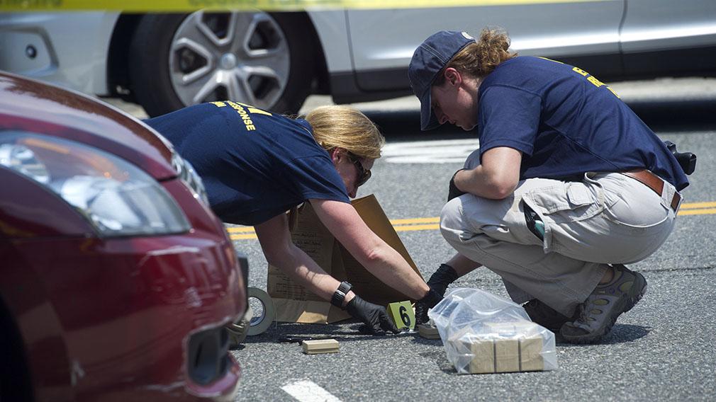 FBI Evidence Response Team members mark evidence at the scene . (AAP)