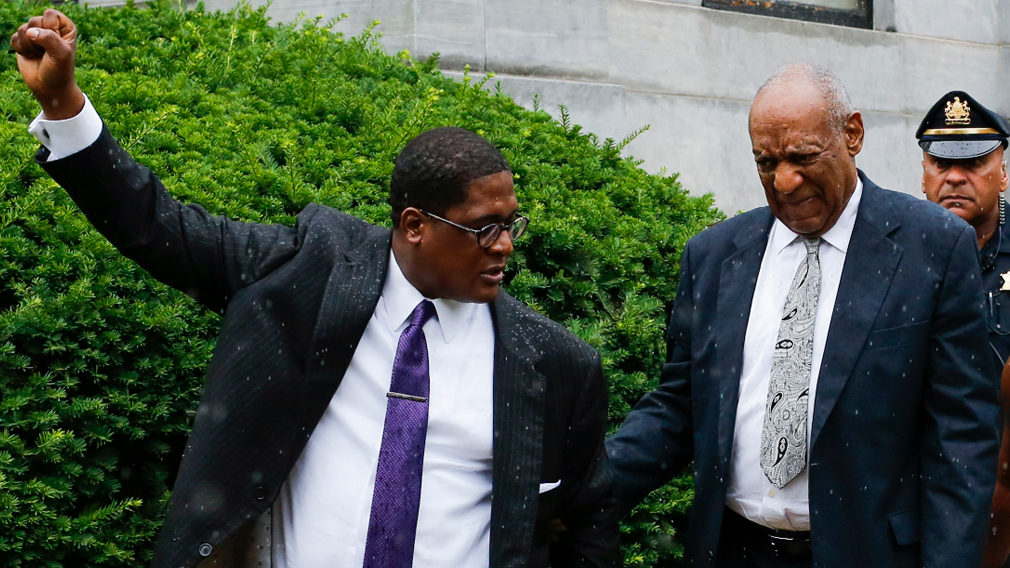 Bill Cosby (right) walks out the courthouse as his spokesman Andrew Wyatt celebrates the mistrial. (AFP)
