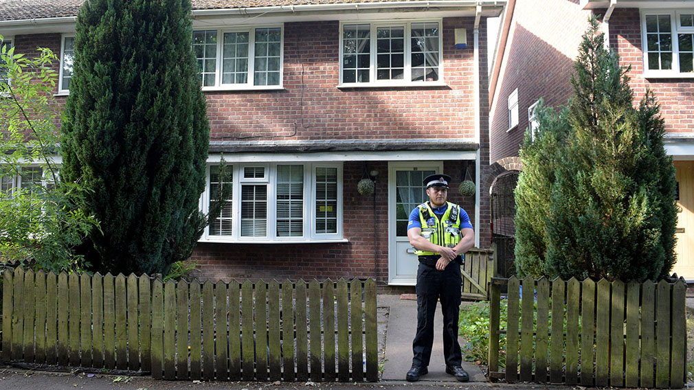 A police officer stands at the front of a residence in Cardiff. (AAP)