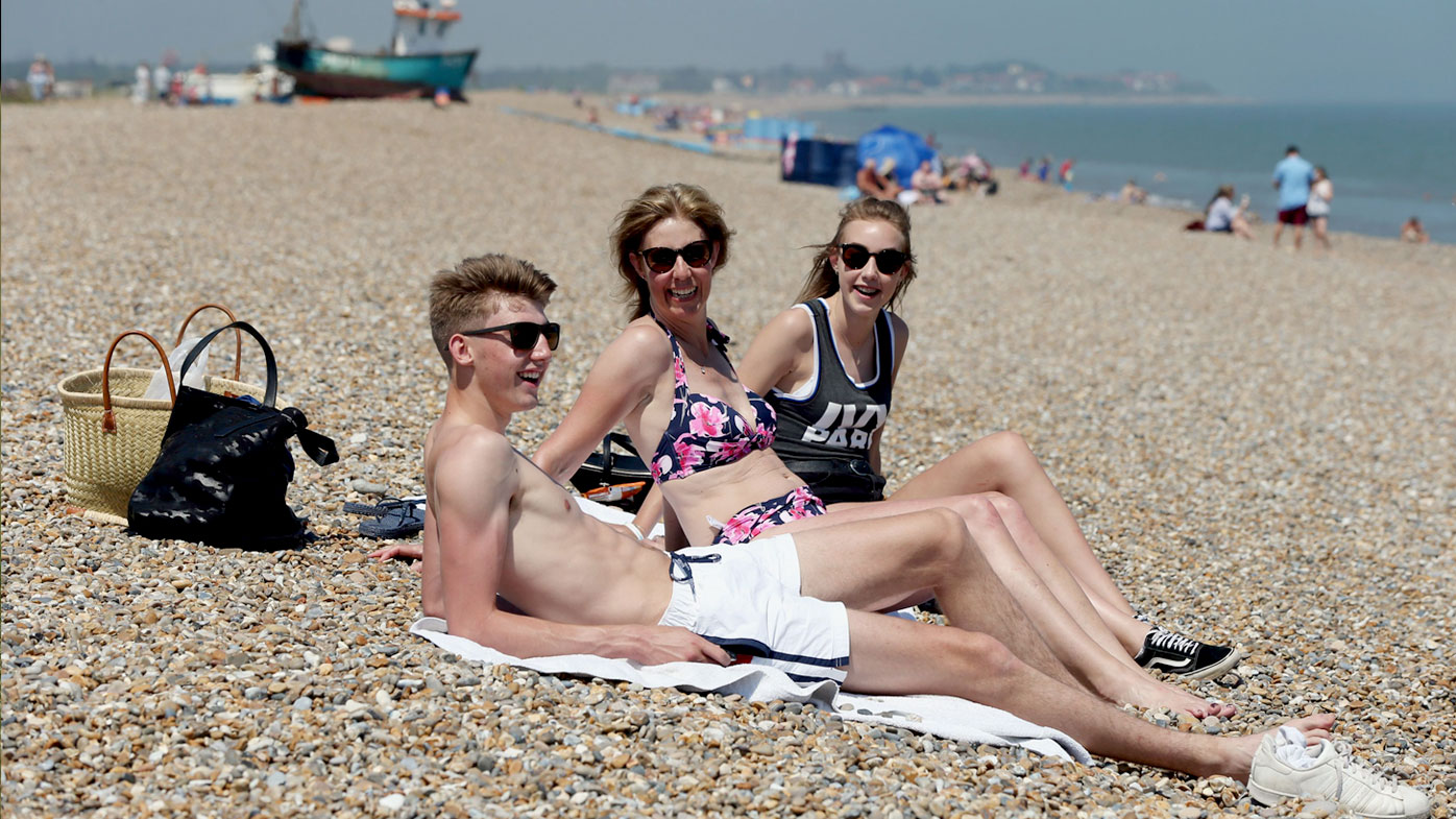 People soak up the sun on a beach in Aldeburgh, Suffolk, in the United Kingdom. (AAP)