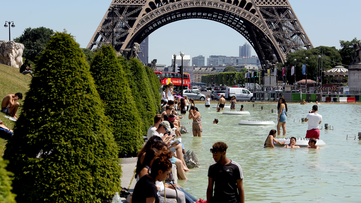 People refresh themselves in the Trocadero fountain in Paris. (AFP)