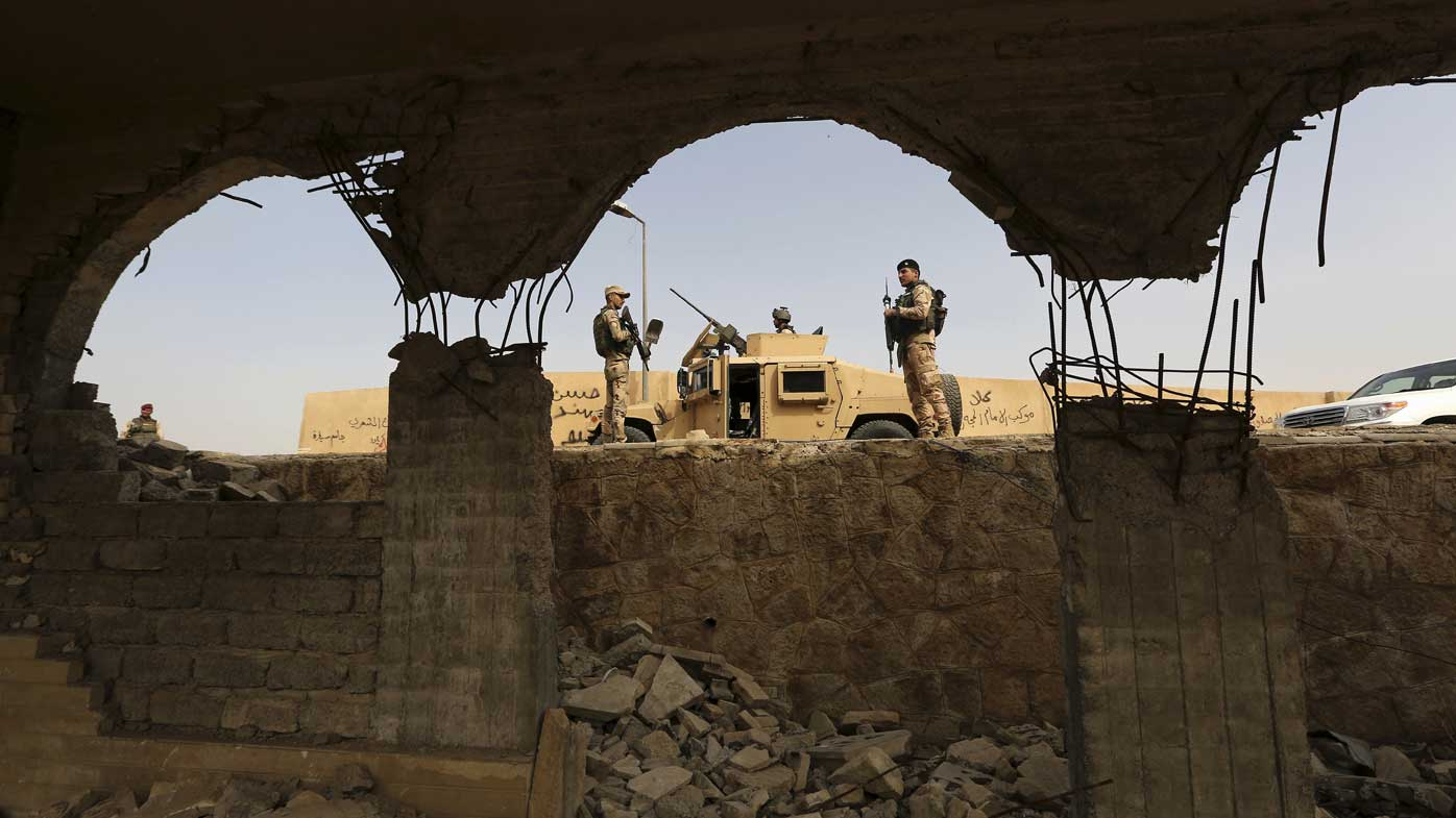 Iraqi troops guard the remains of the Tomb of Jonah mosque. (AAP)