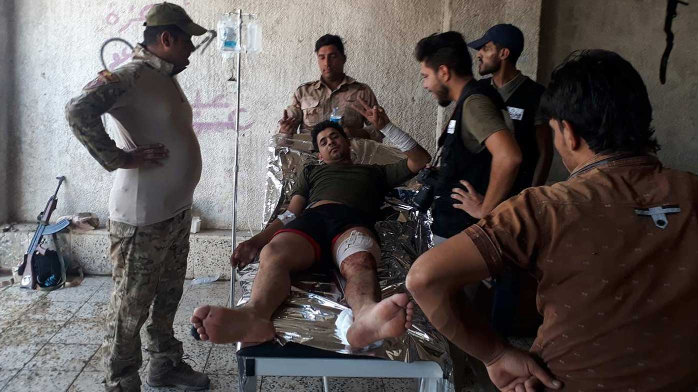 An injured man gestures to the camera in Mosul. (Owen Holdaway)