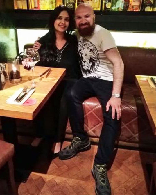 Akbar Badshah, in John's boots, enjoying dinner with his wife. (Akbar Badshah/BBC)