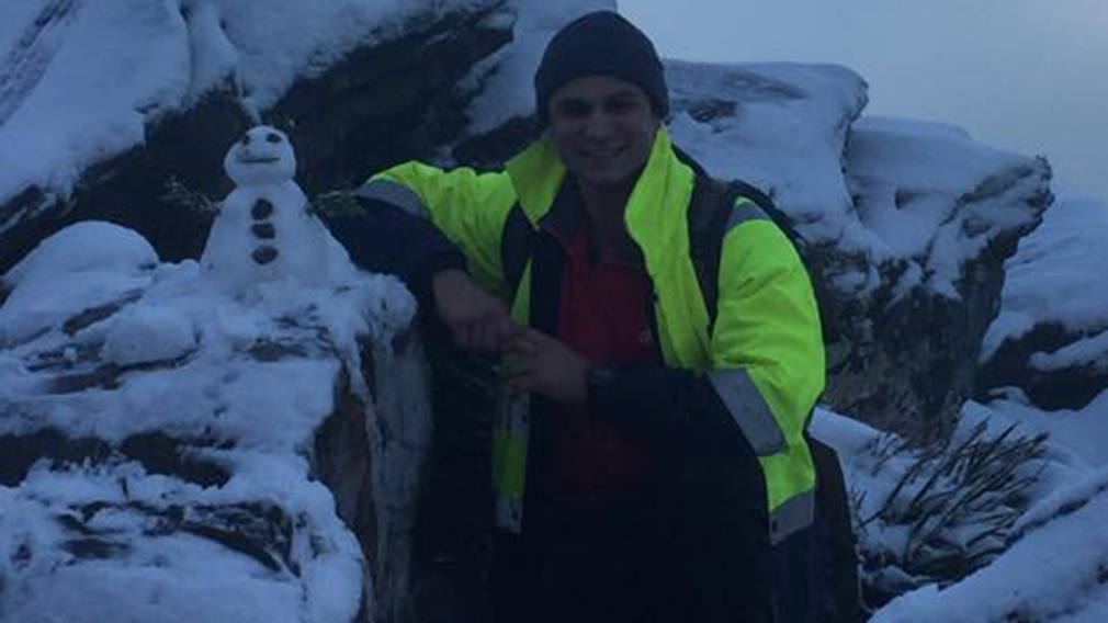 A man poses next to a snowman he built at Bluff Knoll. (Facebook)