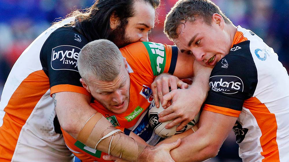 Mitchell Barnett of the Knights is tackled by Aaron Woods and Jacob Liddle of the Tigers