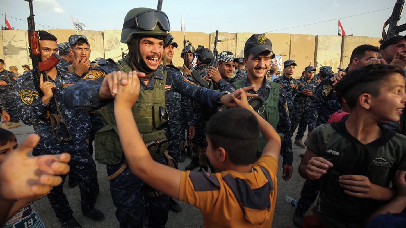Members of the Iraqi federal police dance with children during a celebration in the Old City of Mosul, where the gruelling battle to retake Iraq's second city from Islamic State fighters is now nearing its end. (AFP)