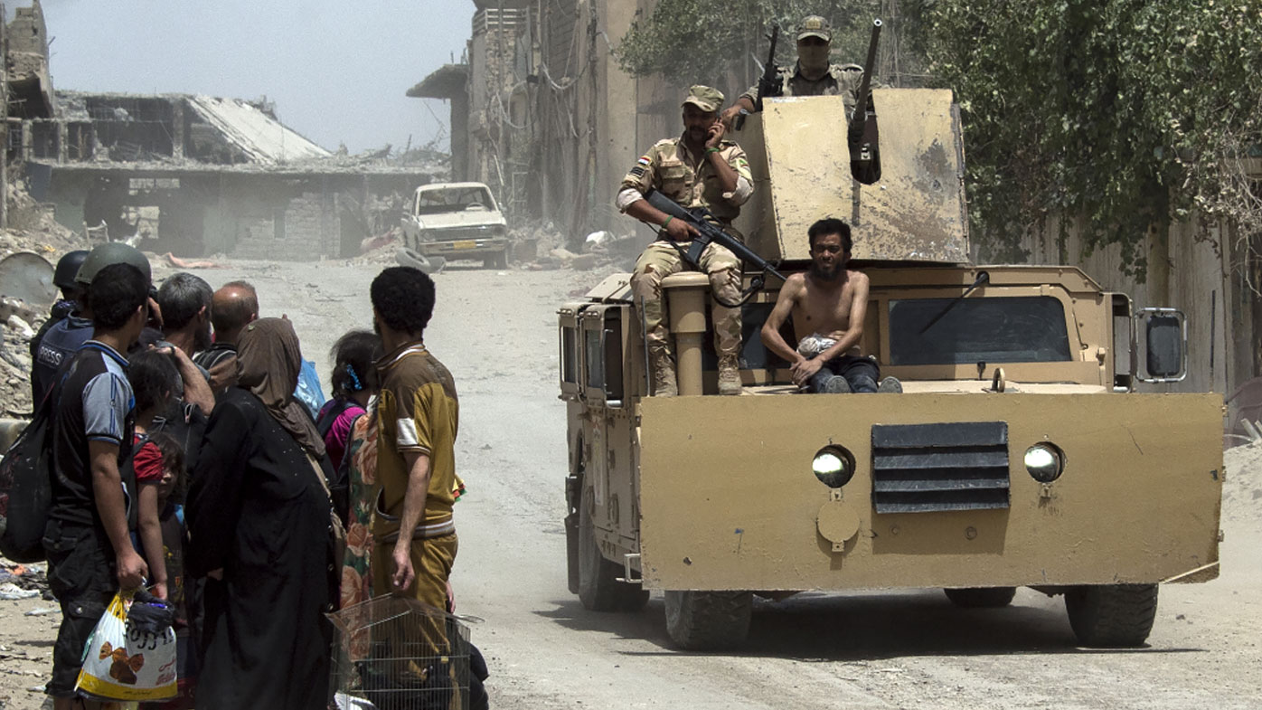 An Iraqi soldier sits on a tank with an alleged Islamic State fighter as civilians flee the Old City of Mosul. (AFP)