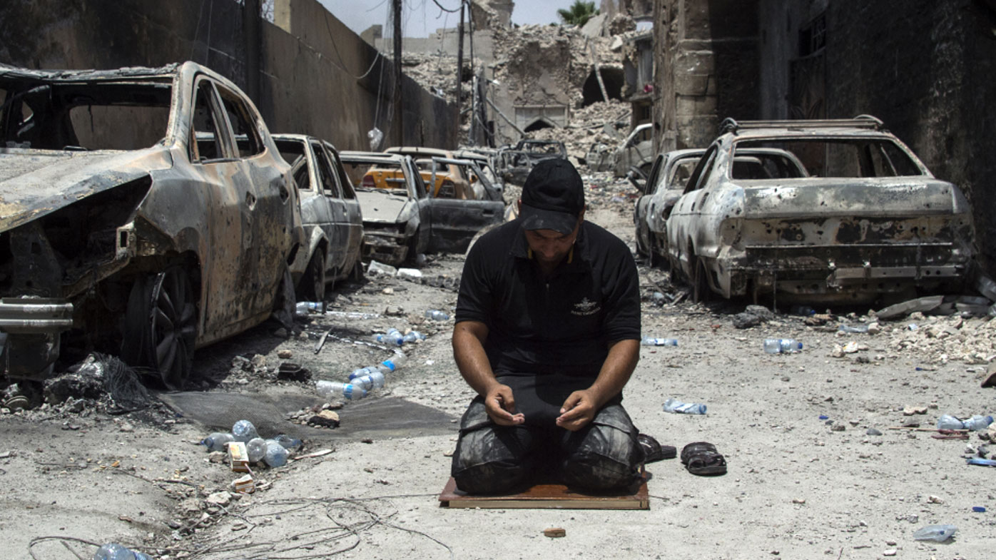 An Iraqi Counter-Terrorism Services member prays in the Old City of Mosul. (AFP)