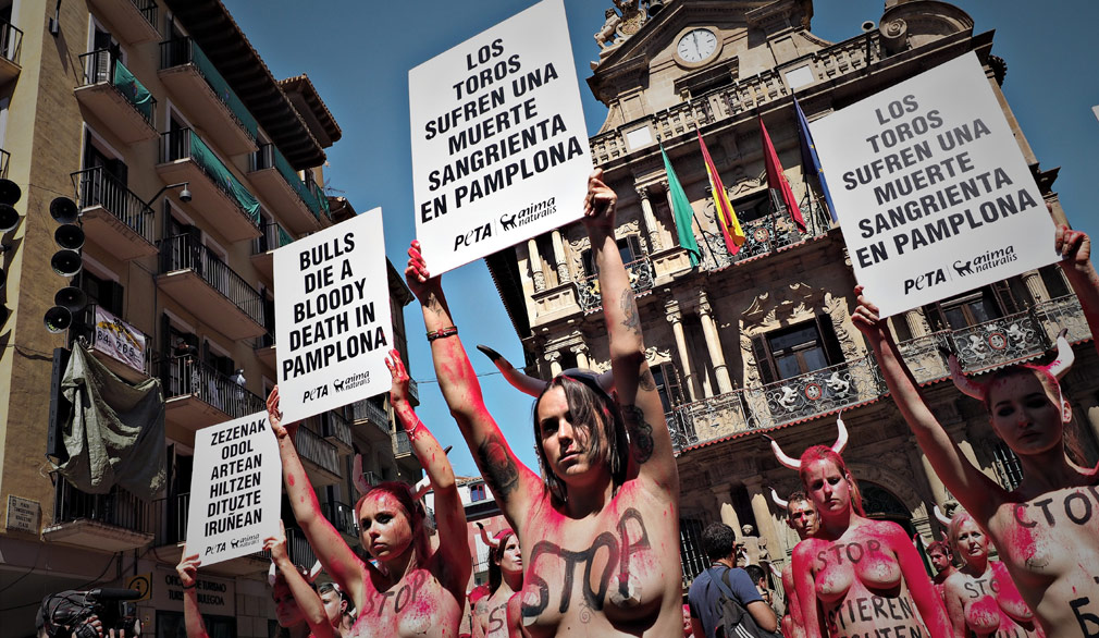 Activists from PETA and AnimaNaturalis hold signs reading 'Bulls die a bloody death in Pamplona' as they stage a protest in Pamplona. (AAP)