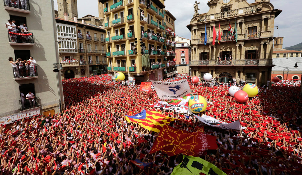 Revellers celebrate the traditional firing of a firecracker, or 'Txupinazo', from the City Hall's balcony which marks the beginning of the Festival of San Fermin 2017. (AAP)