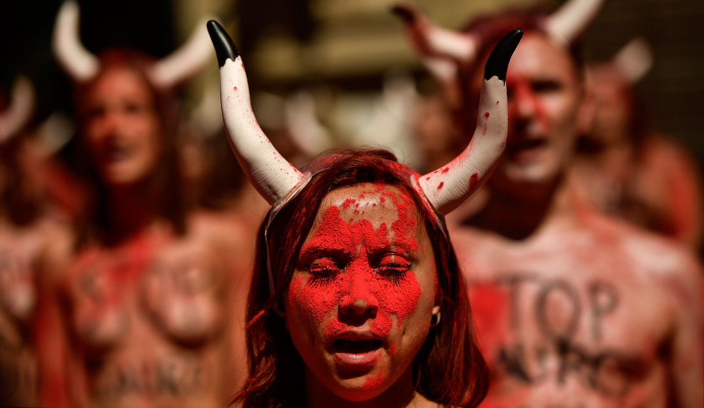 Demonstrators protest against bullfighting cover their bodies with red dust in front of the City Hall a day before of the famous San Fermin festival, in Pamplona. (AAP)