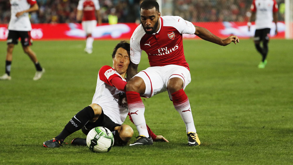 Arsenal's record signing Alexandre Lacazetta shrugs off Wanderers midfielder Jumpei Kusukami. (AAP)