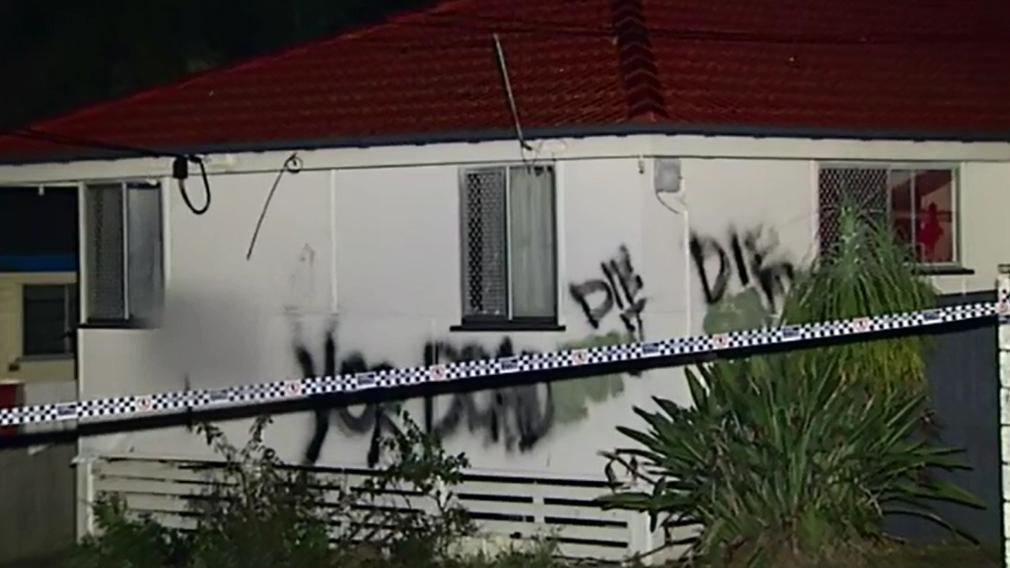 Graffiti can be seen on the burned Woodridge home. (9NEWS)